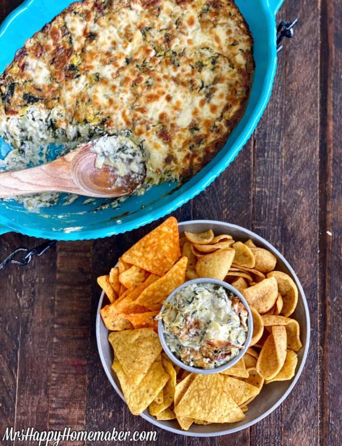 Spinach artichoke alfredo dip in a blue oval casserole dish With a round dip tray with chips beside it