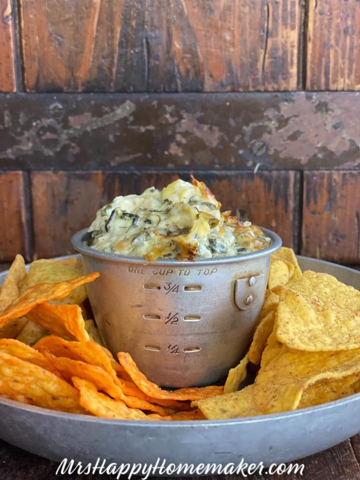 Spinach Artichoke Alfredo Dip in a vintage silver cup surrounded by chips