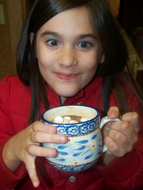 little girl drinking hot cocoa from a blue mug