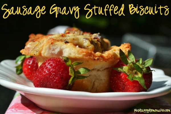 Sausage Gravy Stuffed Buttermilk Biscuits on a white plate surrounded with fresh strawberry garnish