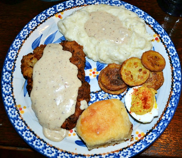 chicken fried steak with gravy served alongside a biscuit, fried squash, deviled egg and mashed potatoes