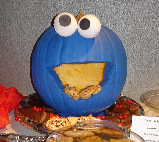 pumpkin carved and painted to look like the Cookie Monster with cookies coming out of it's 'mouth'