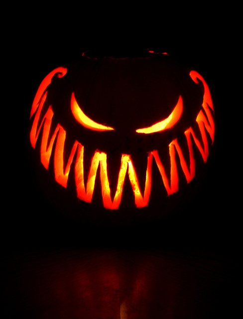 evil face carved jackolantern that is lit up