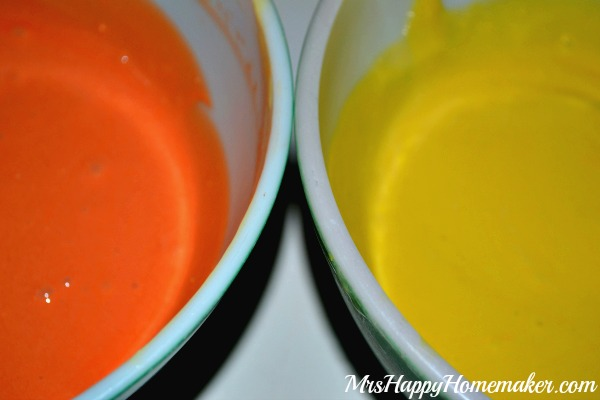 Red and Orange cake batter in two separate bowls to make Candy Corn Poke Cake