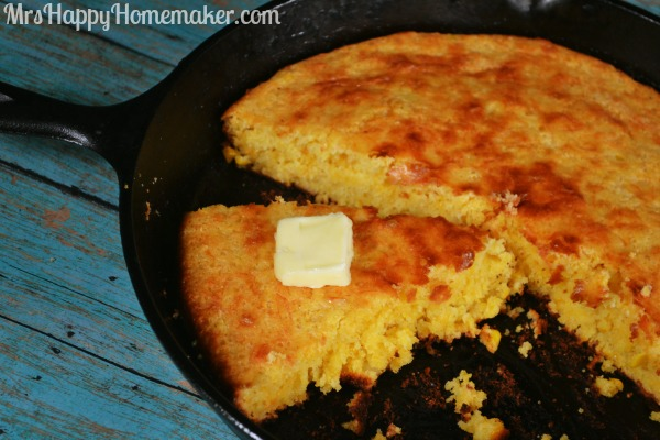 Shortcut Moist & Cheesy Cornbread in a cast iron skillet with a pat of butter