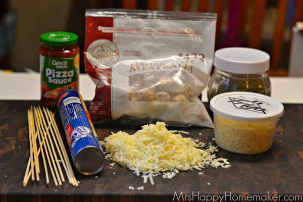 the ingredients for Easy Meatball Sub Kabobs on the countertop - skewers, pizza sauce, breadstick dough, cheese, meatballs, and spices