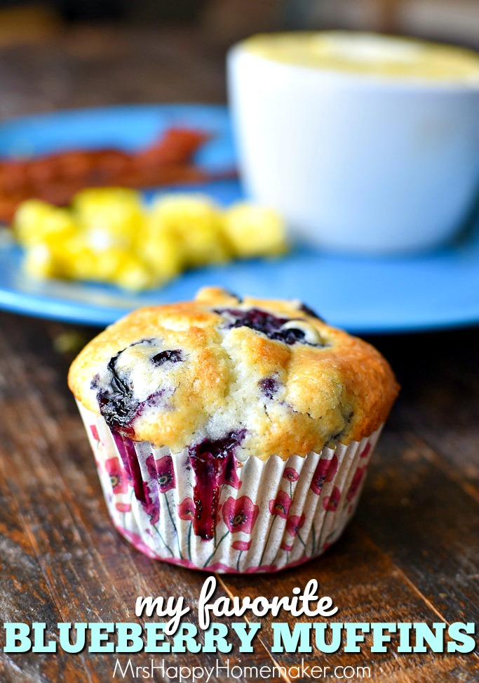 Blueberry muffins on a table with a plate of bacon and eggs behind it