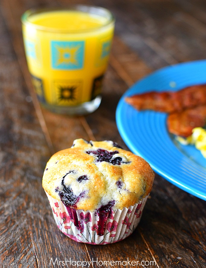 blueberry muffin on a table next to a blue plate with bacon and a cup of orange juice