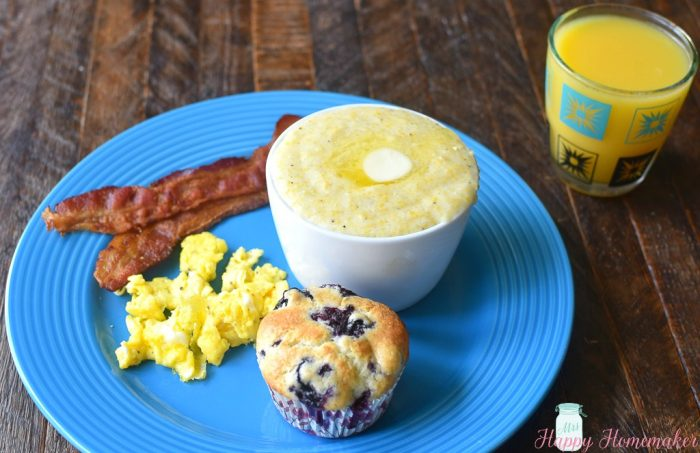 SOUTHERN STYLE CREAMY GRITS on a blue plate with eggs, a muffin and oj | MrsHappyHomemaker.com