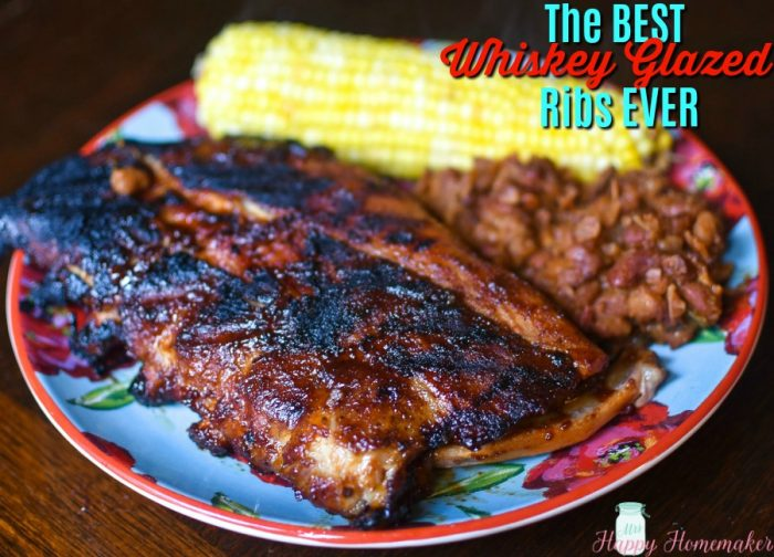 The BEST Whiskey Glazed Ribs on a plate with baked beans and corn on the cob | MrsHappyHomemaker.com
