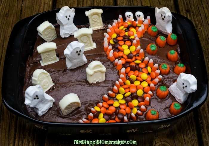 Halloween scene cake with candy ghosts, graves, pumpkins and a sidewalk