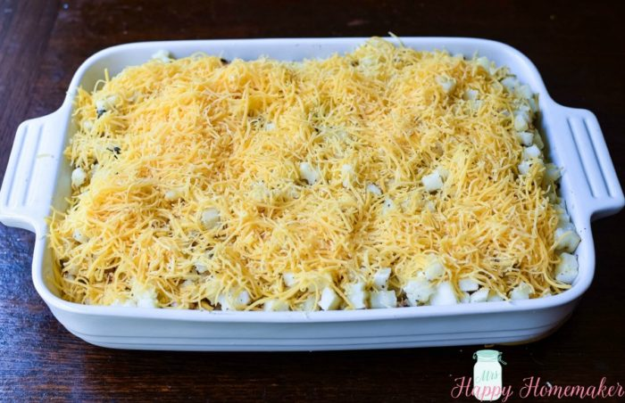 Cheesy Hash Brown Casserole being made - potatoes and cheese in the casserole dish