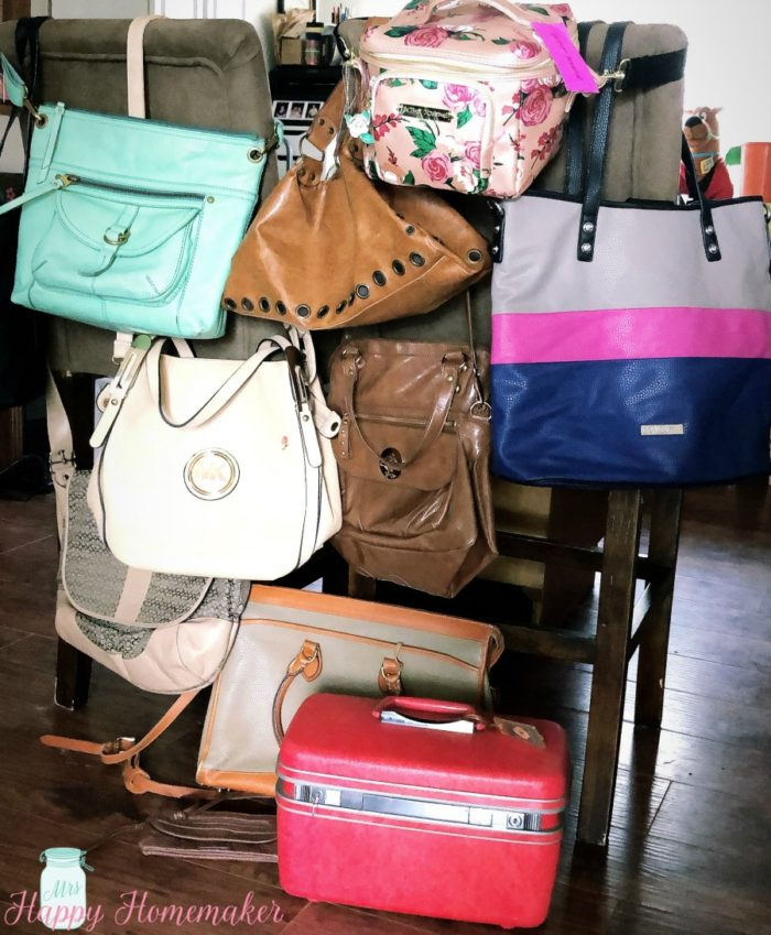 various purses and bags hanging on the back of a chair, purchased from peaches to beaches yard sale 2019