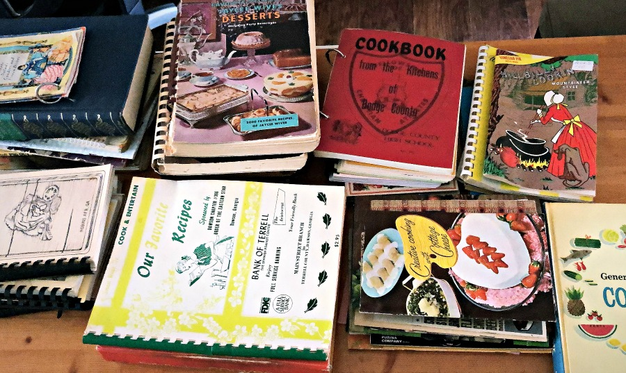 Various vintage cookbooks from Peaches to Beaches yard sale stacked all over a tabletop