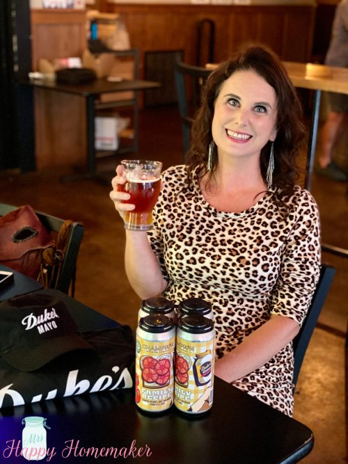 Mrs Happy Homemaker holding Dukes Mayo and Champion Brewery collaboration beer, Family Recipe