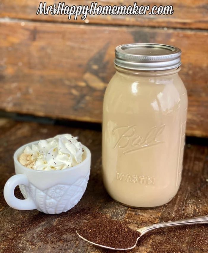 Make ahead lattes - one in a mason jar and one in a white cup topped with whipped cream. There is a spoon with coffee grounds in it beside of it