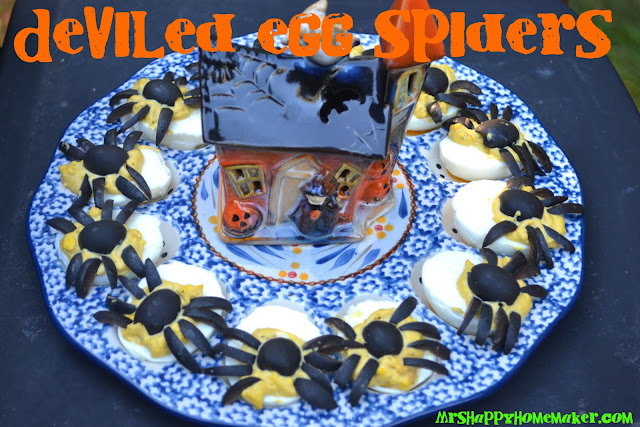 Deviled Egg Spiders on an egg plate surrounding a ceramic mini haunted house decoration