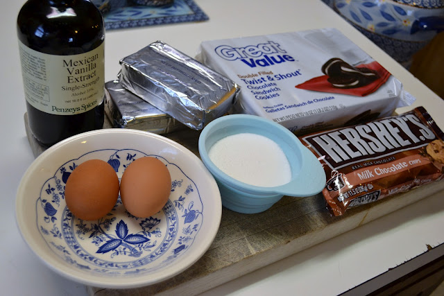 the ingredients for Mini oreo crusted cheesecakes on the counter - vanilla, eggs, sugar, cream cheese, chocolate chips, and Oreos