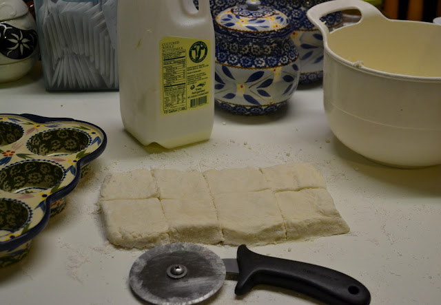 buttermilk biscuit dough, rolled out and being cut into squares on the countertop