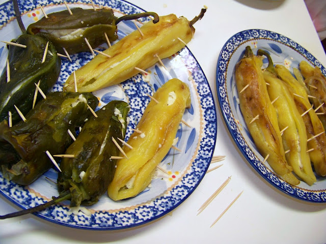 2 plates of Stuffed Chiles Rellenos with toothpicks in them to close them up