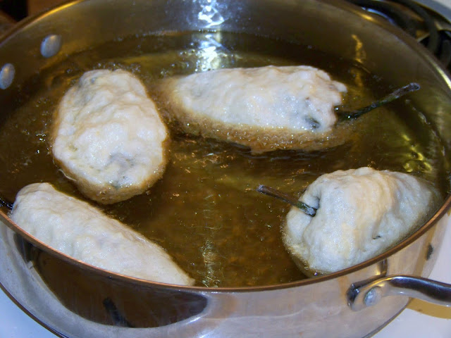 Frying Chiles Rellenos in a skillet of oil